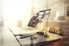 Lugar de trabajo de la oficina con el ordenador portátil y el teléfono elegante en la tabla de madera Fotos de archivo