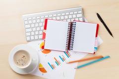 Lugar de trabajo de la oficina con las cartas, el café y la libreta Imágenes de archivo libres de regalías