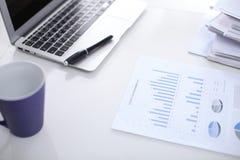 Lugar de trabajo de la oficina con un ordenador portátil y documentos financieros en la tabla reflectora ligera imagen de archivo libre de regalías