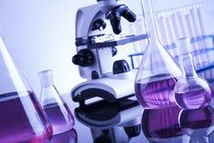 Lugar de trabajo de laboratorio con el microscopio y la cristalería Foto de archivo libre de regalías