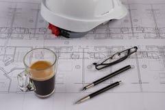 Lugar de trabajo de los arquitectos - modelos arquitectónicos con el casco de seguridad, los vidrios, el café y el lápiz que prop Fotos de archivo libres de regalías