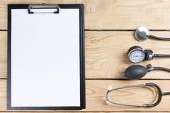 Lugar de trabajo de un doctor Tablero y estetoscopio médicos en fondo de madera del escritorio Visión superior foto de archivo libre de regalías