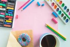 Lugar de trabajo del artista con los equipamientos de dibujo, un buñuelo y un café, y una mofa en blanco de la hoja de papel Imagenes de archivo