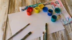 lugar de trabajo del artista: pinturas de la acuarela, brochas, hojas del Libro Blanco, paleta de colores y pintura inacabada Imagen de archivo