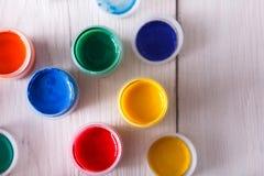 Lugar de trabajo del artista, sistema de pinturas del color en el escritorio de madera Fotos de archivo libres de regalías