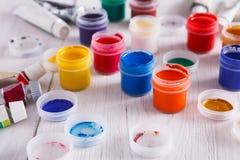 Lugar de trabajo del artista, sistema de pinturas del color en el escritorio de madera Imagen de archivo libre de regalías