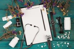 Lugar de trabajo del doctor - estetoscopio, tablero de la medicina, botella, f Imagen de archivo