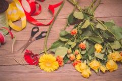 Lugar de trabajo del florista, haciendo el ramo Rosas amarillas y anaranjadas encendido imágenes de archivo libres de regalías