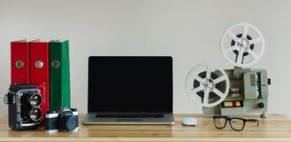 Lugar de trabajo del negocio con el ordenador portátil y objetos retros en la tabla de madera Foto de archivo libre de regalías