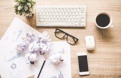 Lugar de trabajo del negocio con el ratón del teclado y las bolas de papel arrugadas, papeles con los gráficos y diagramas Fotografía de archivo libre de regalías