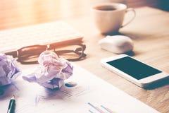 Lugar de trabajo del negocio con el ratón del teclado y las bolas de papel arrugadas, papeles con los gráficos y diagramas para l Imagenes de archivo