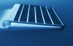 Lugar de trabajo del negocio con el teclado inalámbrico del ordenador en fondo azul de la tabla Escritorio de oficina con el espa Imagenes de archivo