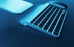 Lugar de trabajo del negocio con el teclado inalámbrico y el ratón del ordenador en fondo azul de la tabla Escritorio de oficina  Imagen de archivo libre de regalías