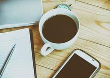 Lugar de trabajo del negocio con la taza de smartphone del café, pluma, cuaderno, fotografía de archivo libre de regalías