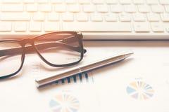 Lugar de trabajo del negocio con los papeles del ratón del teclado con los gráficos y los diagramas Fotos de archivo libres de regalías