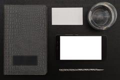 Lugar de trabajo del negocio con un teléfono celular en una tabla de madera negra Fotografía de archivo