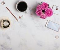 Lugar de trabajo del ` s de la mujer con café, el teléfono y las rosas Fotos de archivo libres de regalías