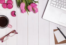 Lugar de trabajo del ` s de la mujer con el ordenador portátil, los tulipanes del café y los macarons rosados Fotografía de archivo libre de regalías