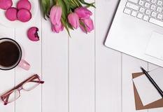 Lugar de trabajo del ` s de la mujer con el ordenador portátil, los tulipanes del café y los macarons rosados Foto de archivo