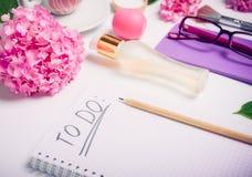 Lugar de trabajo femenino con para hacer la lista, los accesorios cosméticos, el cuaderno, los vidrios, y las flores de la glicin Foto de archivo libre de regalías