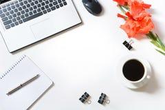 Lugar de trabajo femenino de la oficina con el ordenador portátil, taza de café, accesorios, flor del gladiolo en blanco Visión s Fotos de archivo libres de regalías