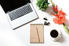 Lugar de trabajo femenino de la oficina con el ordenador portátil, taza de café, accesorios, flor del gladiolo en blanco Visión s Foto de archivo libre de regalías