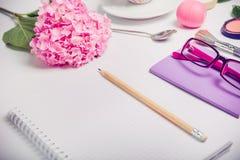 Lugar de trabajo femenino de la visión superior con el cuaderno para planear, el cosmético, el sketchbook, los vidrios, y las flo Imágenes de archivo libres de regalías