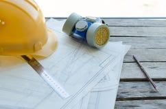Lugar de trabajo de la ingeniería, dibujos, casco protector de la construcción y opinión del respirador del polvo del top Fotografía de archivo libre de regalías