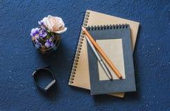 Lugar de trabajo de la mujer con los cuadernos, la pluma, el reloj y el florero con las flores En fondo azul Foto de archivo libre de regalías