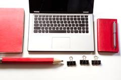 Lugar de trabajo de la oficina con el ordenador portátil, accesorios rojos en blanco Visión superior con el espacio de la copia Fotografía de archivo libre de regalías