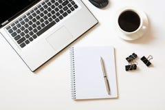 Lugar de trabajo de la oficina con el ordenador portátil, taza del café, accesorios en blanco Visión superior con el espacio de l Imágenes de archivo libres de regalías
