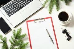 Lugar de trabajo de la oficina con el ordenador portátil, taza del café, accesorios en blanco Visión superior con el espacio de l Imagen de archivo libre de regalías