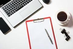 Lugar de trabajo de la oficina con el ordenador portátil, taza del café, accesorios en blanco Visión superior con el espacio de l Imagenes de archivo