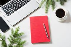 Lugar de trabajo de la oficina con el ordenador portátil, taza del café, accesorios en el fondo blanco Visión superior con el esp Imagenes de archivo