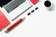 Lugar de trabajo de la oficina con el ordenador portátil, taza del café, accesorios rojos en blanco Visión superior con el espaci Foto de archivo