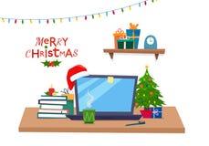 Lugar de trabajo de la oficina de la Navidad Tabla con el ordenador, regalos, árbol de navidad, libros foto de archivo