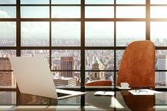 Lugar de trabajo moderno con un ordenador portátil y los accesorios de la oficina en la salida del sol Fotos de archivo libres de regalías