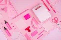 Lugar de trabajo moderno de la juventud - efectos de escritorio rosados de neón como modelo decorativo en el fondo rosado, visión Fotografía de archivo libre de regalías