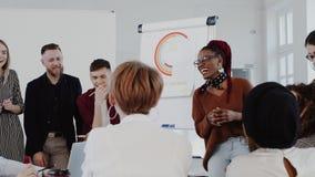 Lugar de trabajo multi?tnico sano Jefe africano joven de la mujer que habla en la reunión del equipo en la EPOPEYA ROJA moderna d metrajes