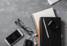 Lugar de trabajo plano del negocio de la endecha con el cuaderno, tableta, teléfono, vidrios en un fondo gris Imagenes de archivo