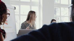 Lugar de trabajo sano Reunión principal rubia hermosa joven del equipo de la mujer de negocios del CEO en la EPOPEYA ROJA moderna almacen de video