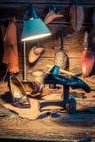 Lugar de trabajo viejo del zapatero con las herramientas, zapatos a reparar imágenes de archivo libres de regalías