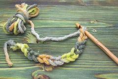 Lugar de trabalho A foto do close up de faz crochê a corrente Rústico fazer crochê a linha e um gancho de bambu Bola morna do fio Imagem de Stock