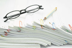 Lugar del lápiz y de las gafas en la pila de papeleo del blanco de la sobrecarga Imagen de archivo