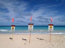 Lugar dos sinais de avisos do Lifeguard na areia na praia Fotografia de Stock
