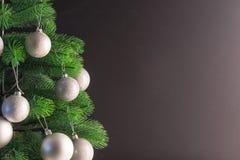 Lugar para su texto, fondo negro hermoso con un árbol de navidad adornado adornado con las bolas de plata, espacio de la copia Imagenes de archivo