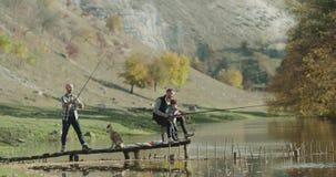 Lugar que sorprende para pescar dos hombres y a un niño pequeño que consiguen listos a coger los pescados del lago, perro fornido almacen de metraje de vídeo