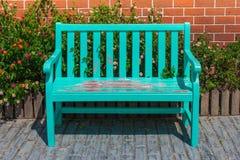 Lugar verde del banco de madera en la calzada o el sendero concreta en el parque público fotografía de archivo libre de regalías
