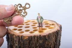 Lugares chaves e pequenos da estatueta do homem no log de madeira fotografia de stock royalty free
