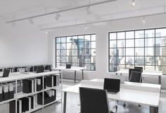 Lugares de trabajo en una oficina moderna brillante del espacio abierto del desván Tablas equipadas de los ordenadores portátiles Fotografía de archivo libre de regalías